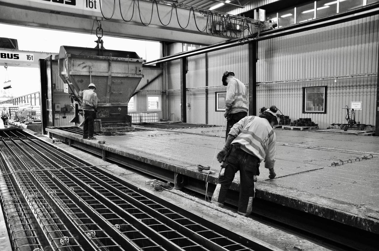 Gråtonad bild på arbetet som pågår i en pålfabrik.